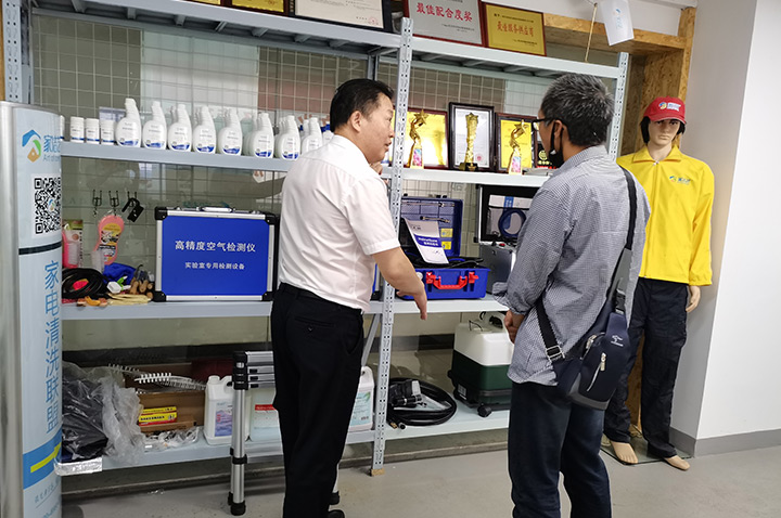 家洁艺工作人员向客户展示家电清洗从业相关设备、药剂